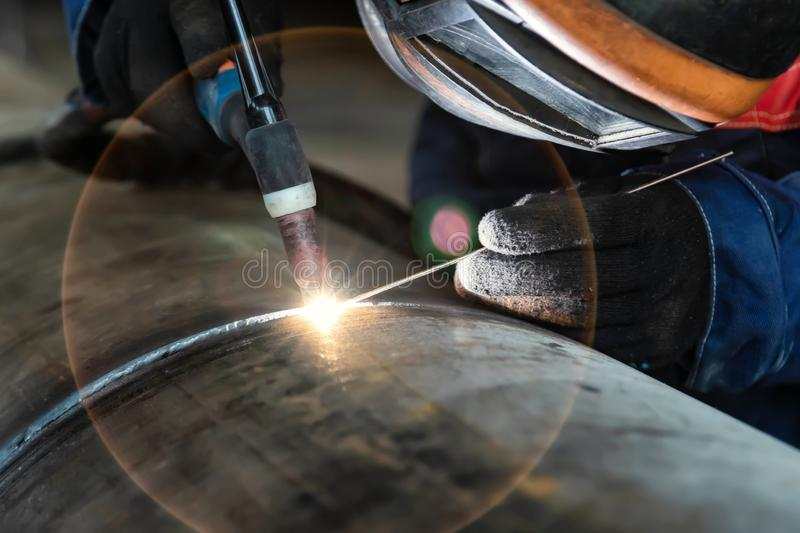 Welder, arc welding and weld seam close-up. Assembly of pipeline assemblies in the Assembly shop using argon-arc welding. Welder, arc welding and weld seam close royalty free stock photo