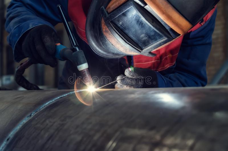Welder, arc welding and weld seam close-up. Assembly of pipeline assemblies in the Assembly shop using argon-arc welding. Welder, arc welding and weld seam close stock photo