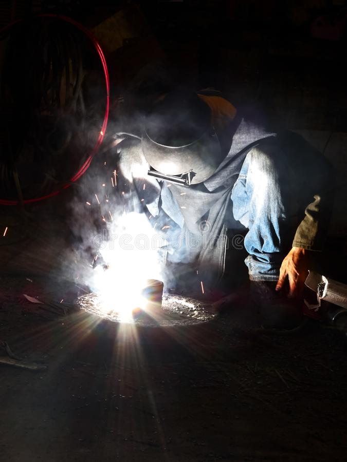 Welder in Asia working with little protective gear royalty free stock photo