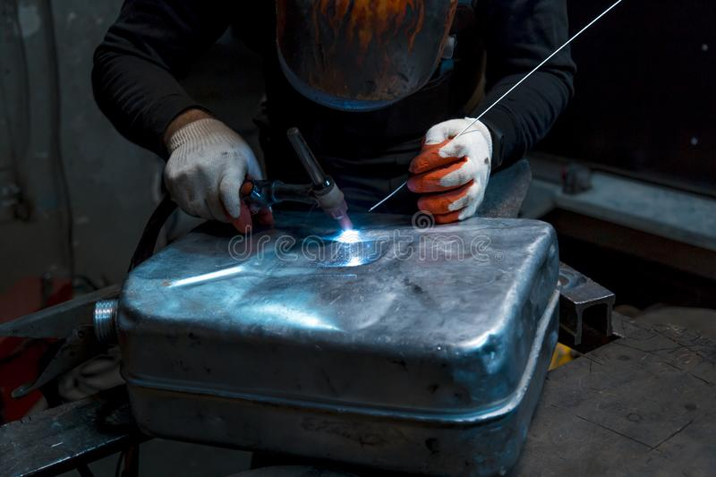 Argon-arc welding welder at the workplace welds the part. The welder ignites the arc and begins welding the aluminum canister with argon arc welding stock photography