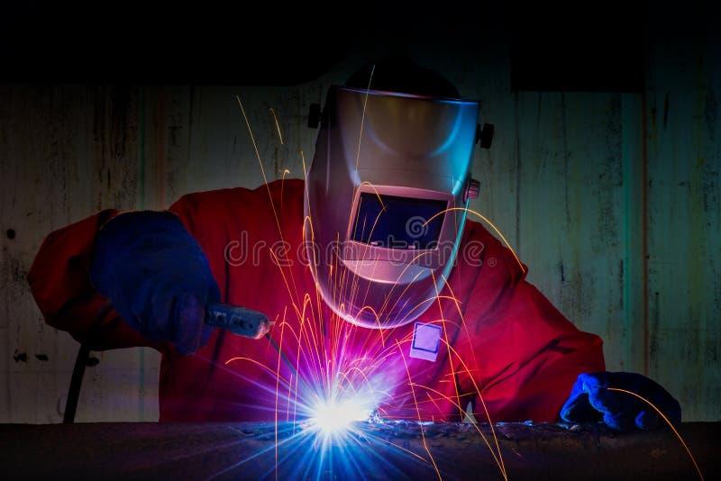 Welder Industrial automotive part in factory. Welder at work welding splatter royalty free stock image