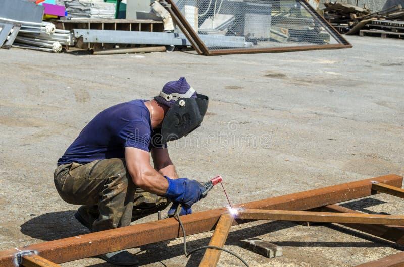Welder på arbetssvetsningen en järnkonstruktion i ett metalllager arkivbilder