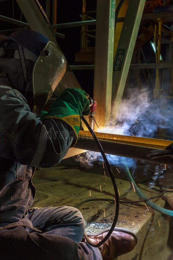 Welder perform welding to the metal plate at roof floor of manufacturing factory by using steel welding electrode in offshore oil stock images