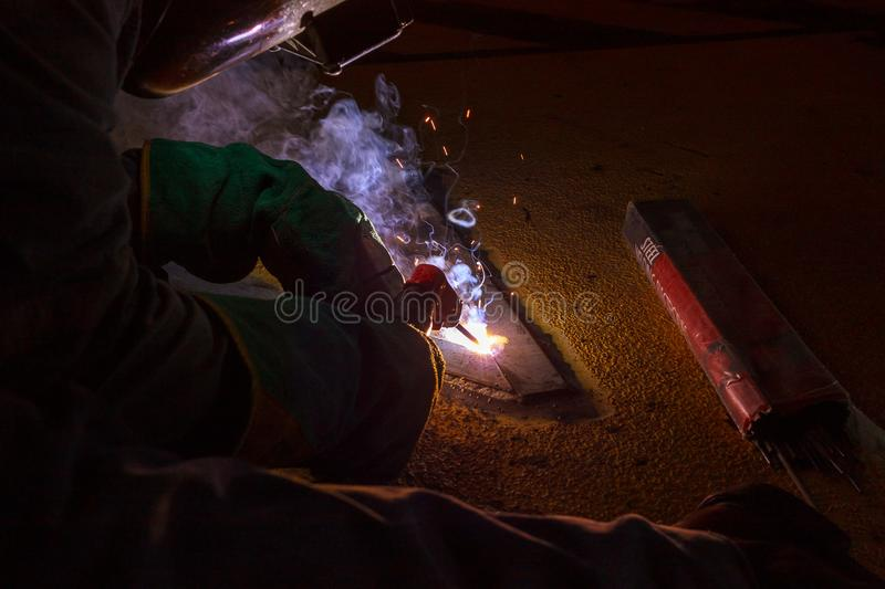 Welder perform welding to the metal plate at roof floor of manufacturing factory by using steel welding electrode in offshore oil stock photography