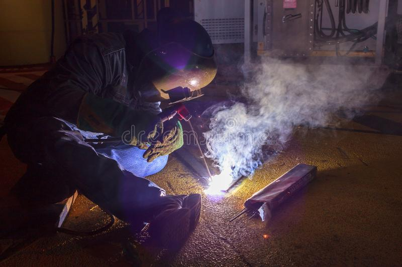 Welder perform welding to the metal plate at roof floor of manufacturing factory by using steel welding electrode in offshore oil stock photo