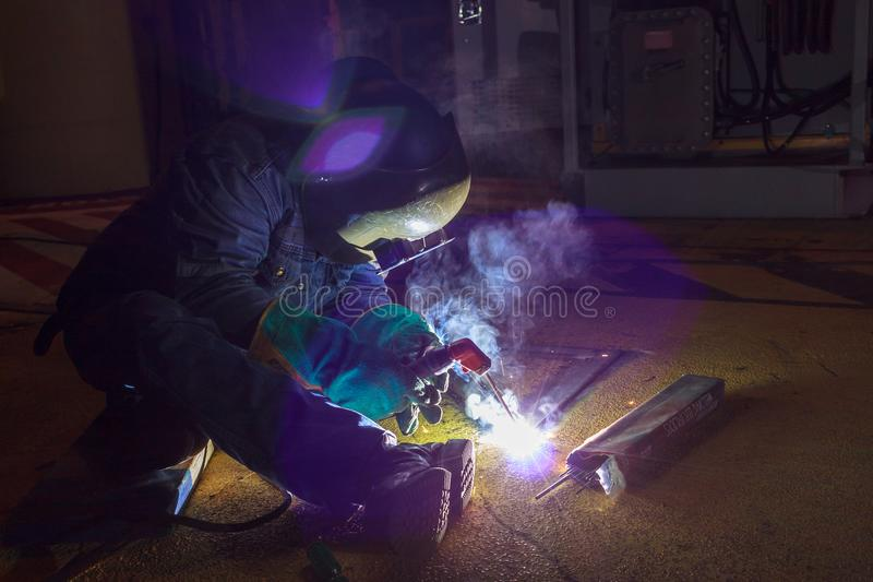 Welder perform welding to the metal plate at roof floor of manufacturing factory by using steel welding electrode in offshore oil royalty free stock photography