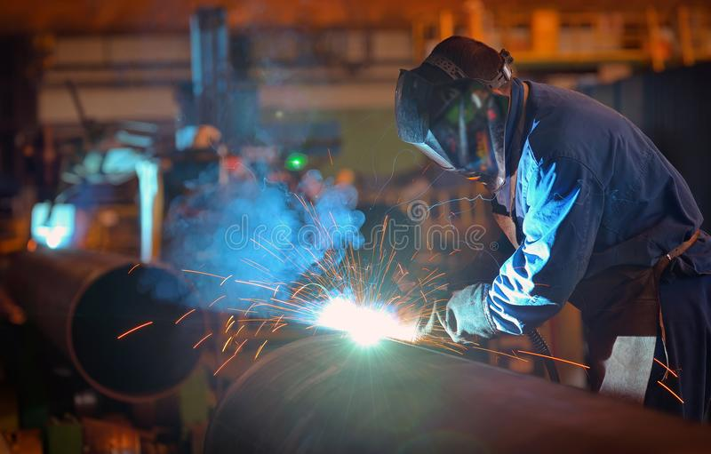 Welder performs welding large diameter pipe stock photos