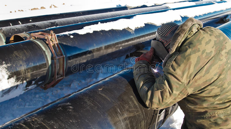 Welder performs welding pipeline in winter conditions stock photo