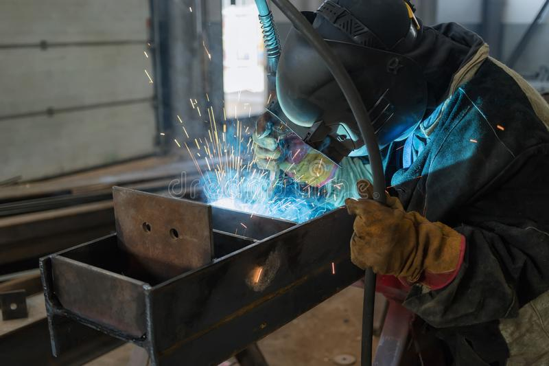 Welder performs welding work of metal structures royalty free stock images