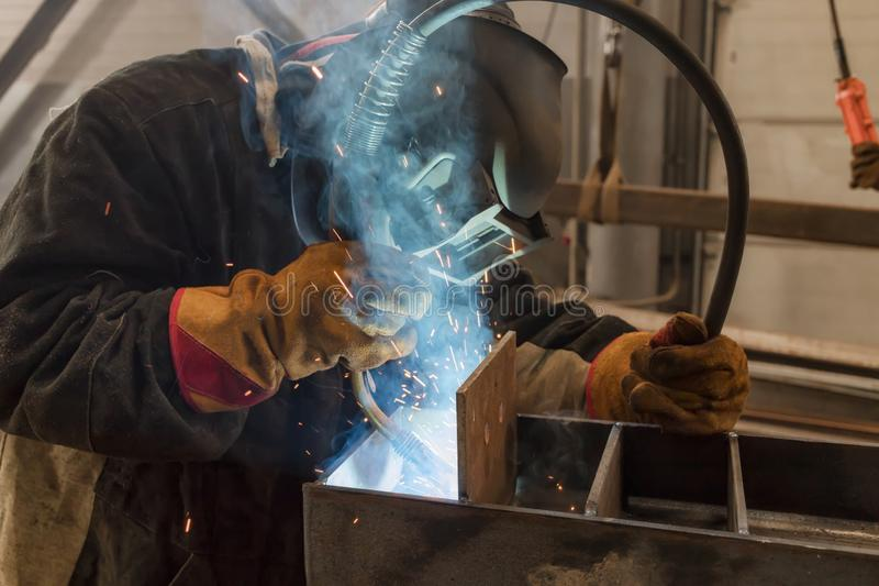 Welder performs welding work of metal structures royalty free stock photos