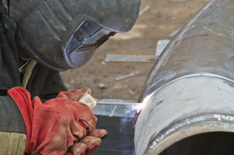 Welder performs welding works on pipelines stock photos