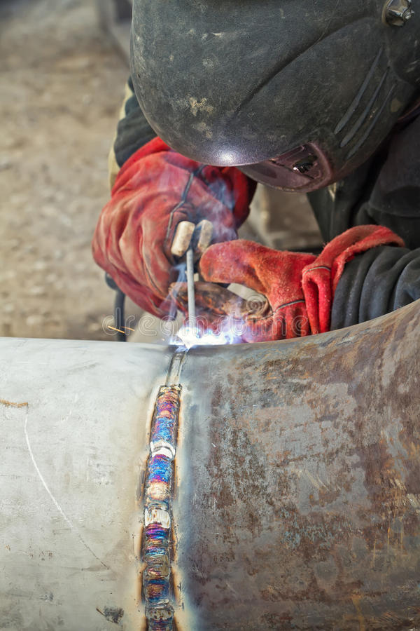 Welder performs welding works on pipelines royalty free stock images