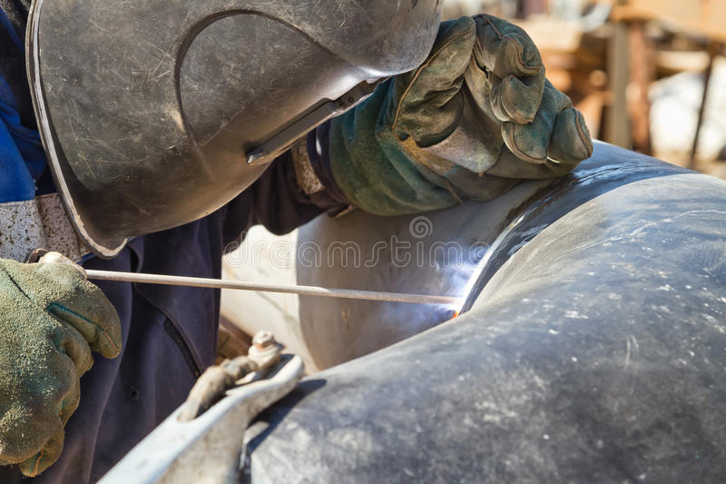 Welder performs welding works on pipelines royalty free stock photos
