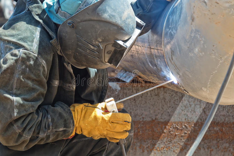 A welder in protective clothing performs the welding of the n element of the process pipeline stock photography