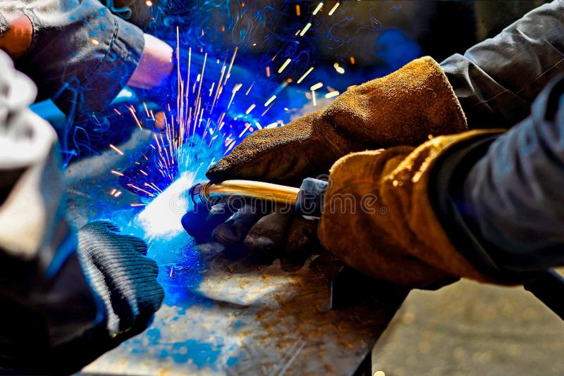 A welder in protective gloves produces a metal connection by electrical welding stock images