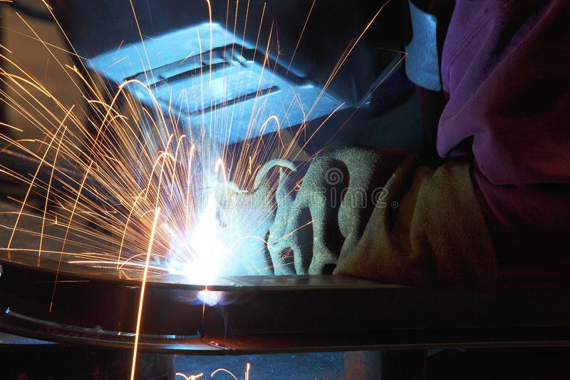 A welder using a wire feed welder to join two pieces of metal together. stock photos