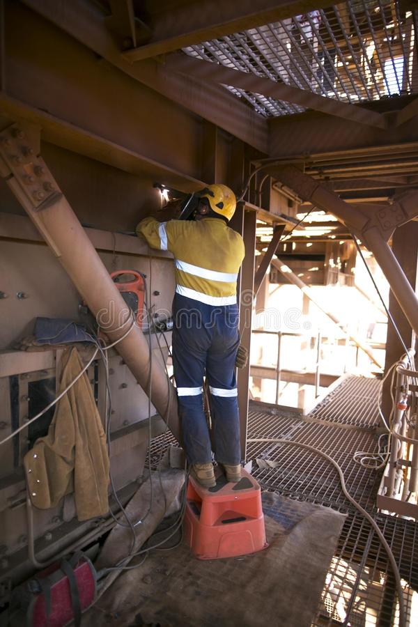 Welder wearing full safety equipment glove, mask using and standing up on industry safety steps while commencing welding parent me. Tal repairs hot work at stock photos