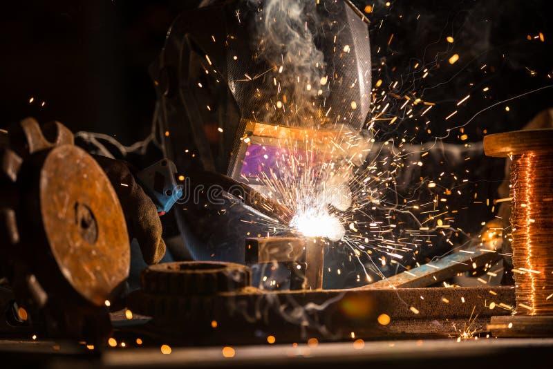 Welder is welding metal part in factory royalty free stock photography