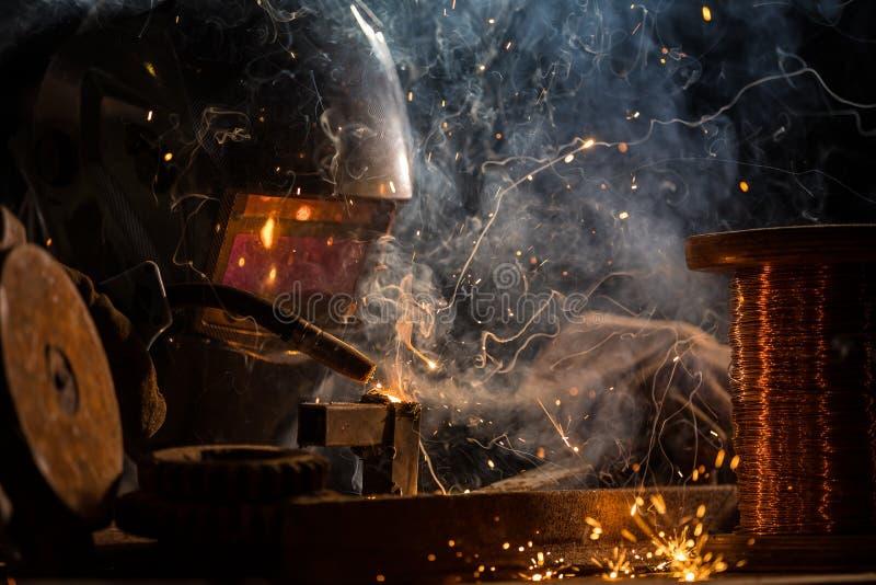 Welder is welding metal part in factory stock photography