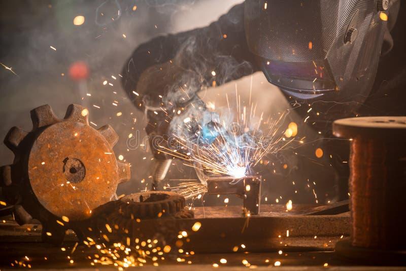 Welder is welding metal part in factory royalty free stock images