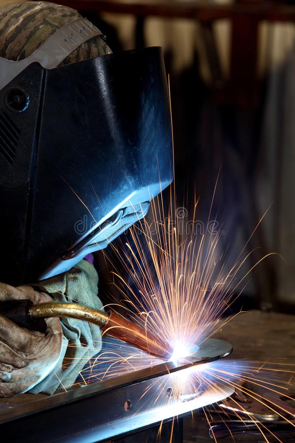 A welder using a wire feed welder to join two pieces of metal together. stock image