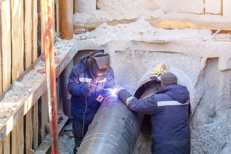 Welder welding water or gas steel pipeline with assistant worker in trench. City underground utilitites renewal and replacemen. T industry construction metal stock images