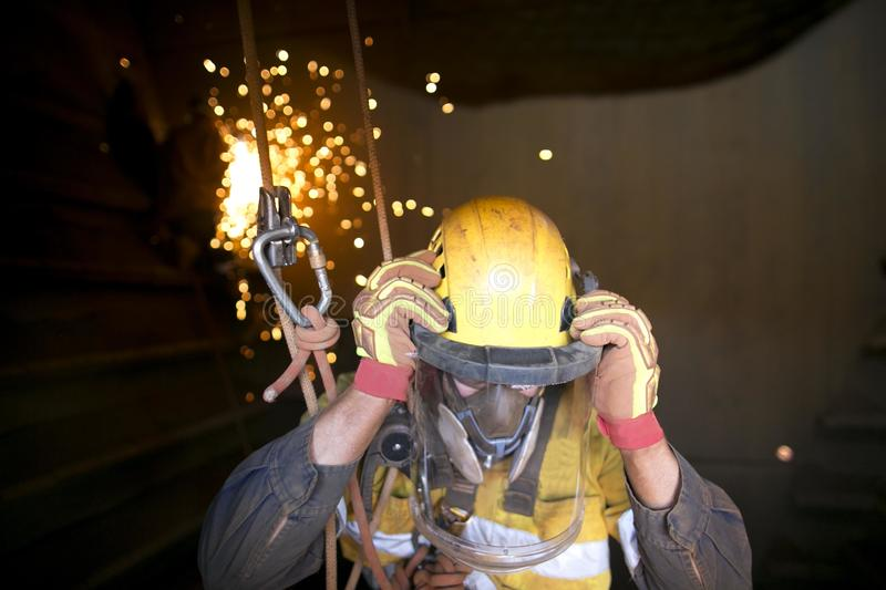Welder worker hanging working at height wearing helmet using face shield safety equipment protection. Rope access construction welder worker hanging working at royalty free stock image