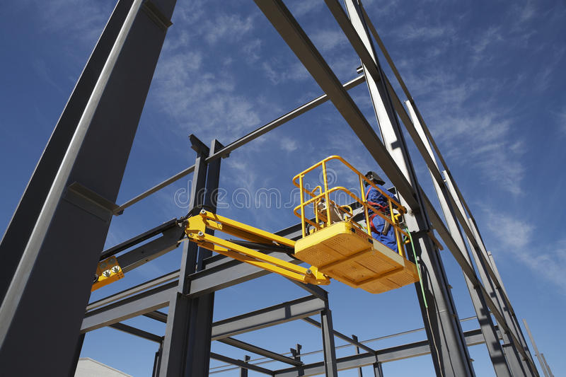 Welder Working From Cherry Picker. On steel framing structure stock images