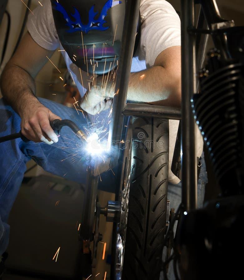 Welder working on motorcycle stock photo