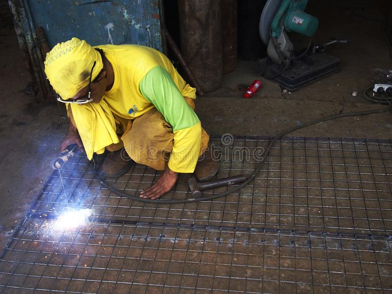A welder works on a fence in front of a shop. stock photo