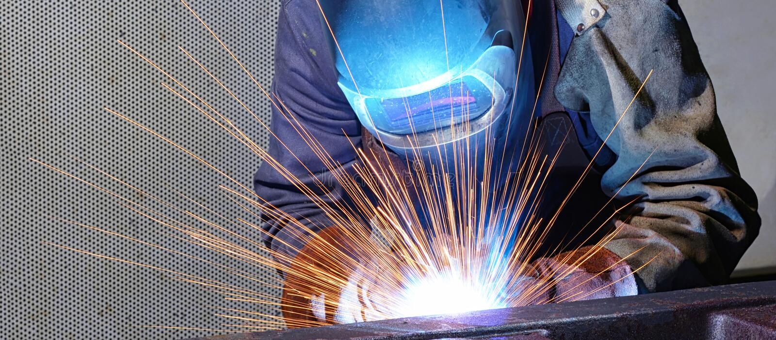 Welder works in an industrial company - production of steel comp stock photos