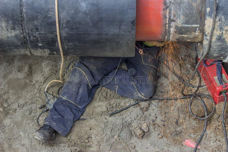 Welderarbetare som maler svetsningen i dike under rörledningen royaltyfria bilder