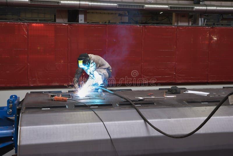 Welderman i arbete som svetsar ett stålark vid TIG- eller PERUKsvetsningtillvägagångssätt, genom att använda en svetsningtråd och fotografering för bildbyråer