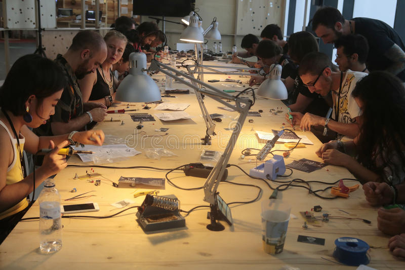Welding components workshop. A group of people takes part in a workshop to build electronic music devices and equipment during a masterclass at Sonar advanced stock images