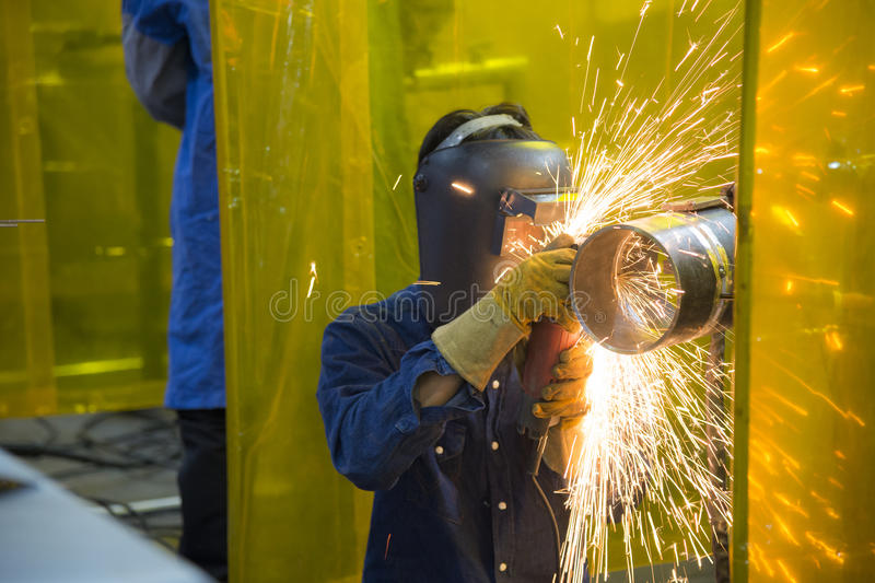 The welding craftsman grinding the steel tube stock image