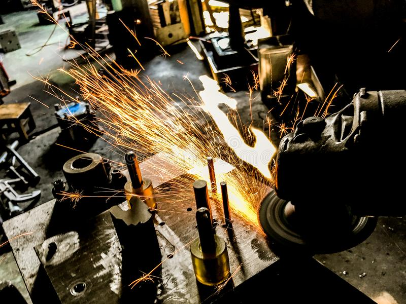 Welding and grinding within the manufacturing process Sparks and smoke. stock image