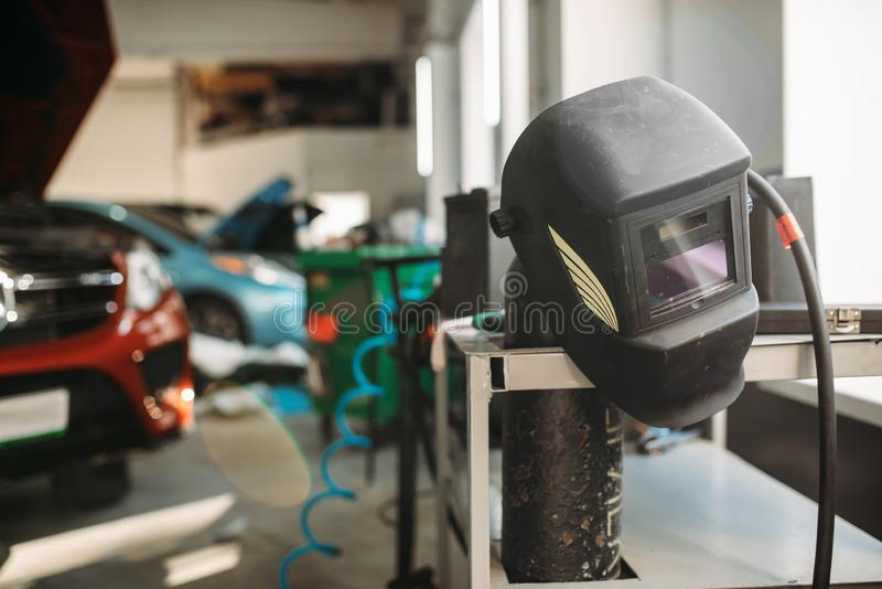 Welding helmet in car service , nobody. Professional auto-service tools and equipment, auto body works royalty free stock images