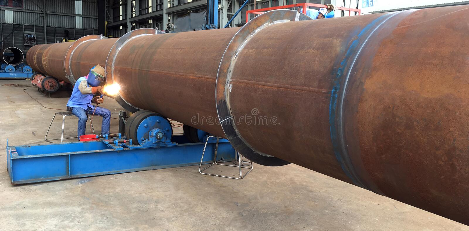 Welding person weld oil and gas offshore industry big pipe work. Welding technician weld big pipe work in oil and gas offshore industry in a fabrication yard royalty free stock photo