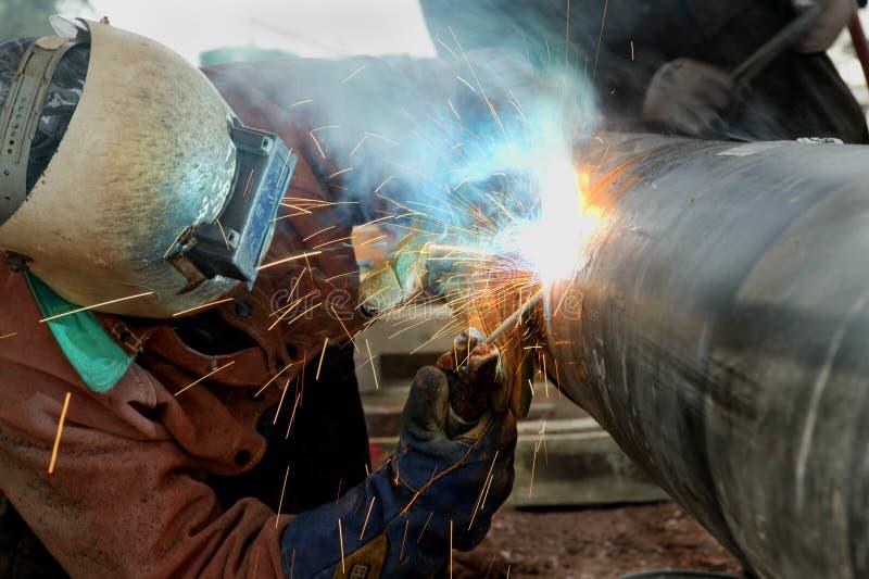 Welding Pipeline. Welder at Work on Outdoor Pipeline Project stock photo