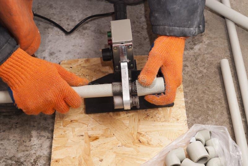 Welding of polypropylene pipes. Plumber weld two pieces of polypropylene pipes royalty free stock image