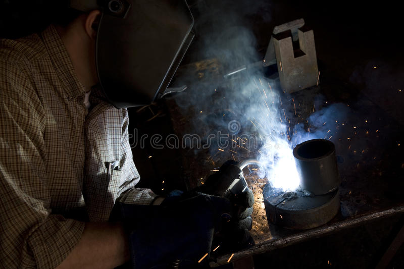 Welding side view. A side view of a man working on a project welding with his mask on and sparks and smoke in the air royalty free stock image