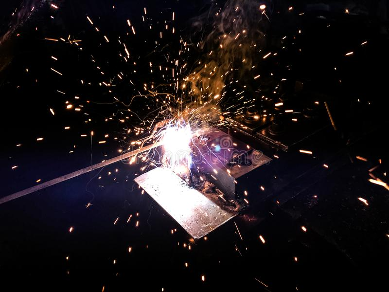 Welding of steel. Sparks and smoke from welding of steel royalty free stock image