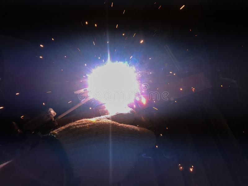 Welding of steel. Sparks and smoke from welding of steel stock photo