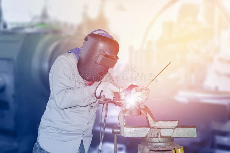 Welding Tig in factory. Male in face mask welding with Tig gas argon and arc welding in factory on Monochrome background stock photography