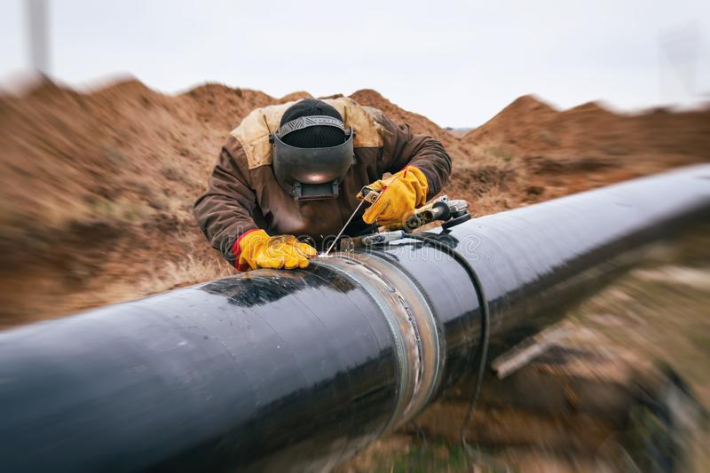 Welding works on gas pipeline. Welder mounts in the trunk pipeline electrochemical protection stock images