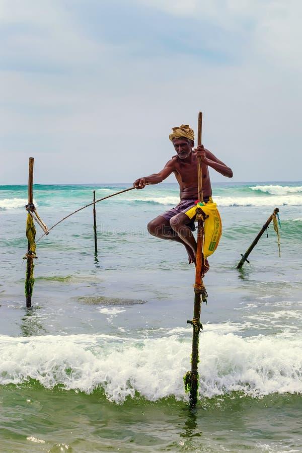 WELIGAMA, SRI LANKA - VERS EN DÉCEMBRE 2013 : Pêcheur d'échasse photo stock