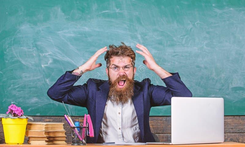 Welke stomme gedachte Agressieve uitdrukking van de mensen zit de gebaarde leraar de achtergrond van het klaslokaalbord Onplezier stock fotografie
