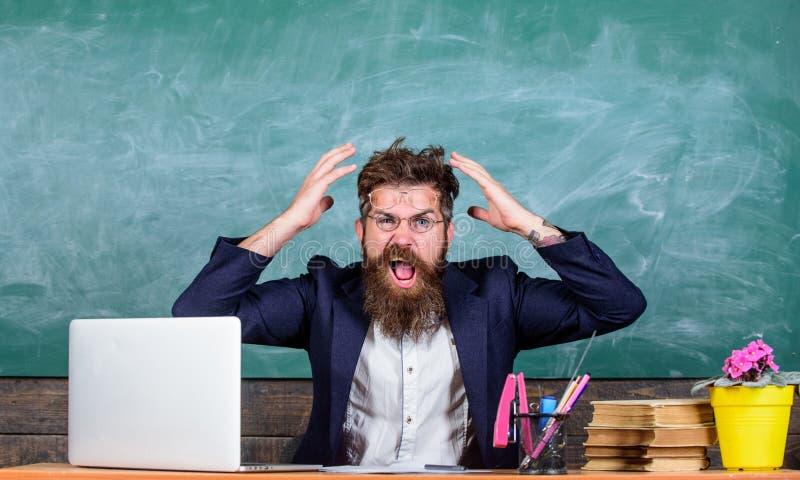 Welke stomme gedachte Agressieve uitdrukking van de mensen zit de gebaarde leraar de achtergrond van het klaslokaalbord Onplezier royalty-vrije stock foto's