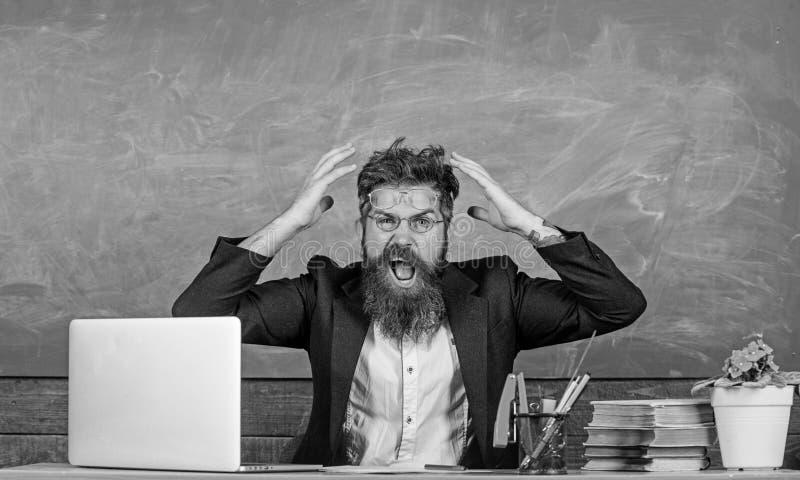 Welke stomme gedachte Agressieve uitdrukking van de mensen zit de gebaarde leraar de achtergrond van het klaslokaalbord Onplezier stock afbeelding