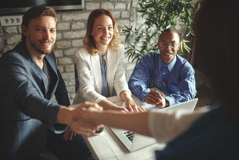 Welkom aan boord! zakenman het schudden handen met glimlach in bureau royalty-vrije stock foto